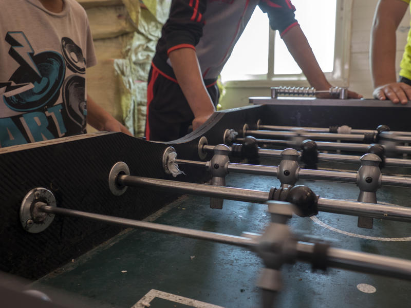 Unaccompanied children living in Azraq refugee camp spend the afternoon playing foosball with friends at a recreation room.