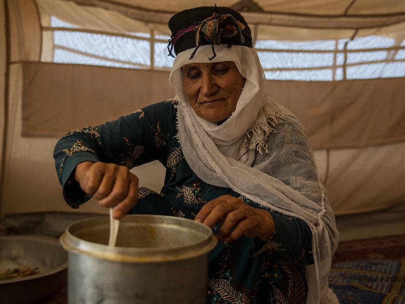 A woman cooks over a small steel pot.