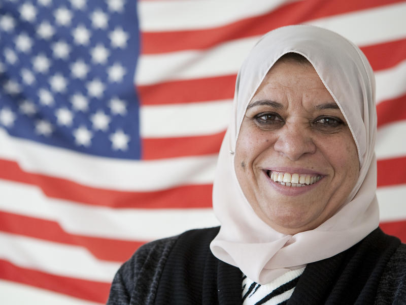 New American citizen stands in front of American flag