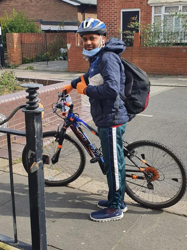 Md Mominul Hamid on his bike in his neighbourhood in Newcastle, where he delivers food packages to the community during the pandemic.