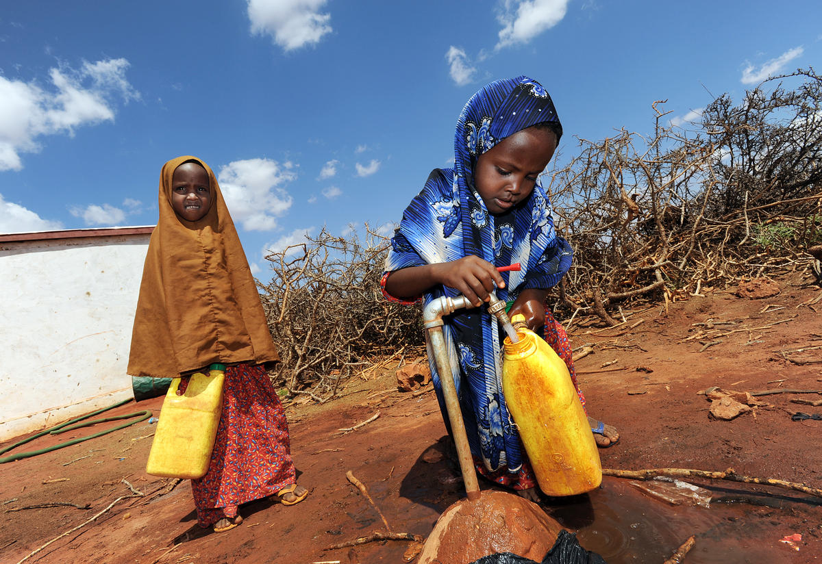 Two children fetching water at an IRC-installed water tap in Darussalam village, Galmudug state.