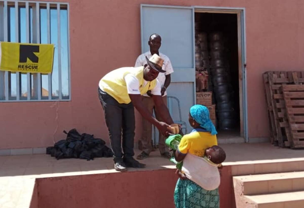 A man working for the IRC leans down to hand a mother and a child a small parcel