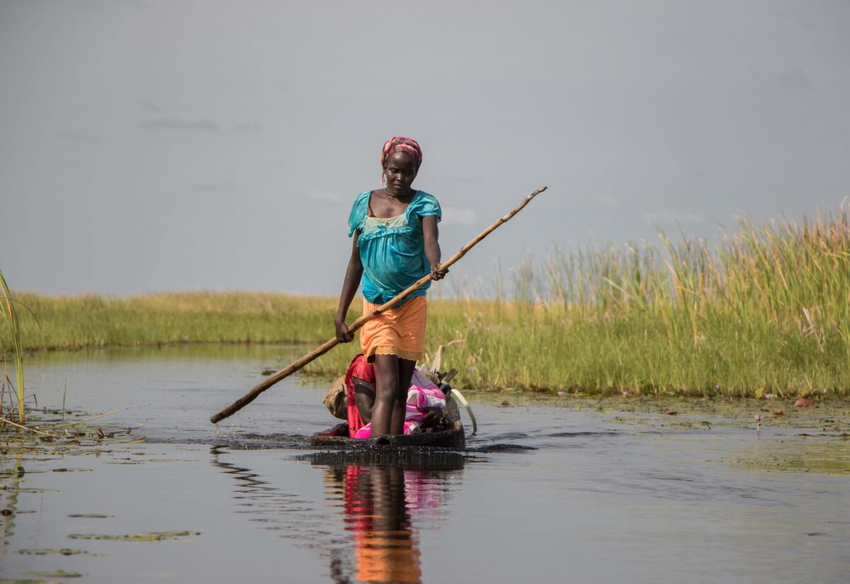 A woman paddles down a river on a small wooden boat