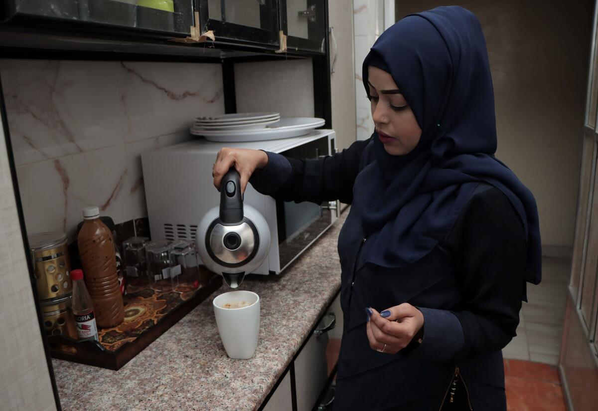 Bushra pouring hot water into a cup