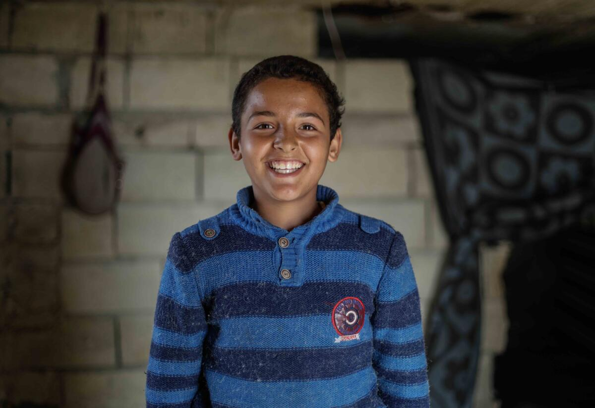 10-year-old Tareq smiles at the camera.