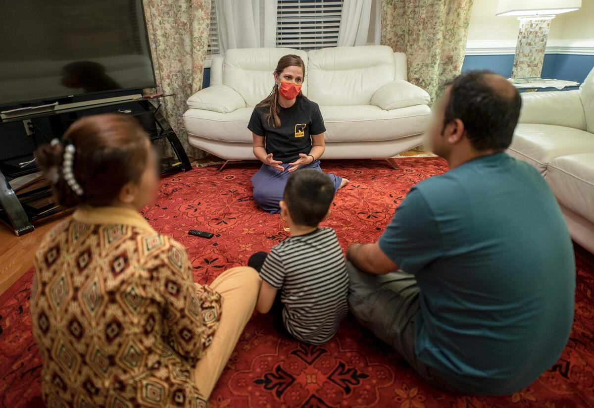 Jessica Carey, an IRC employment specialist, sits on the floor facing an Afghan family who have their backs to the camera