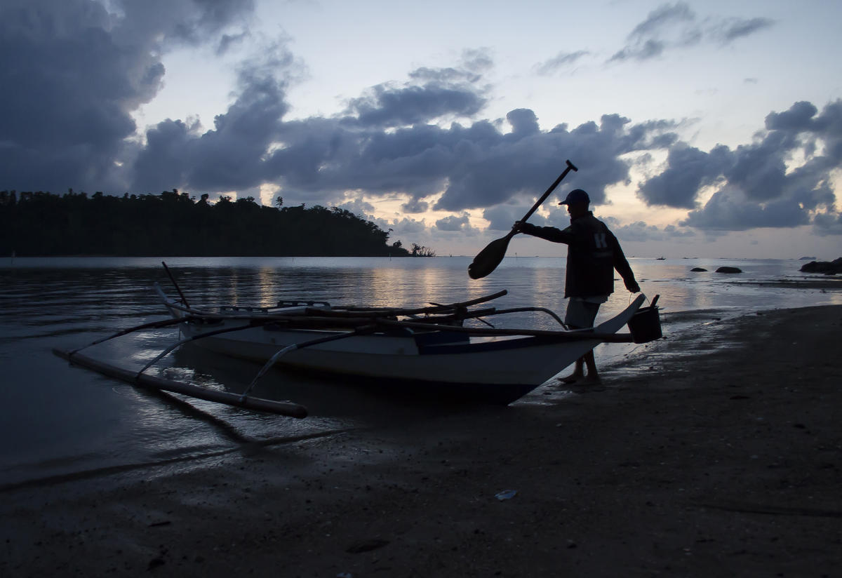 Fisherman gets into his boat as the sun rises on the beach