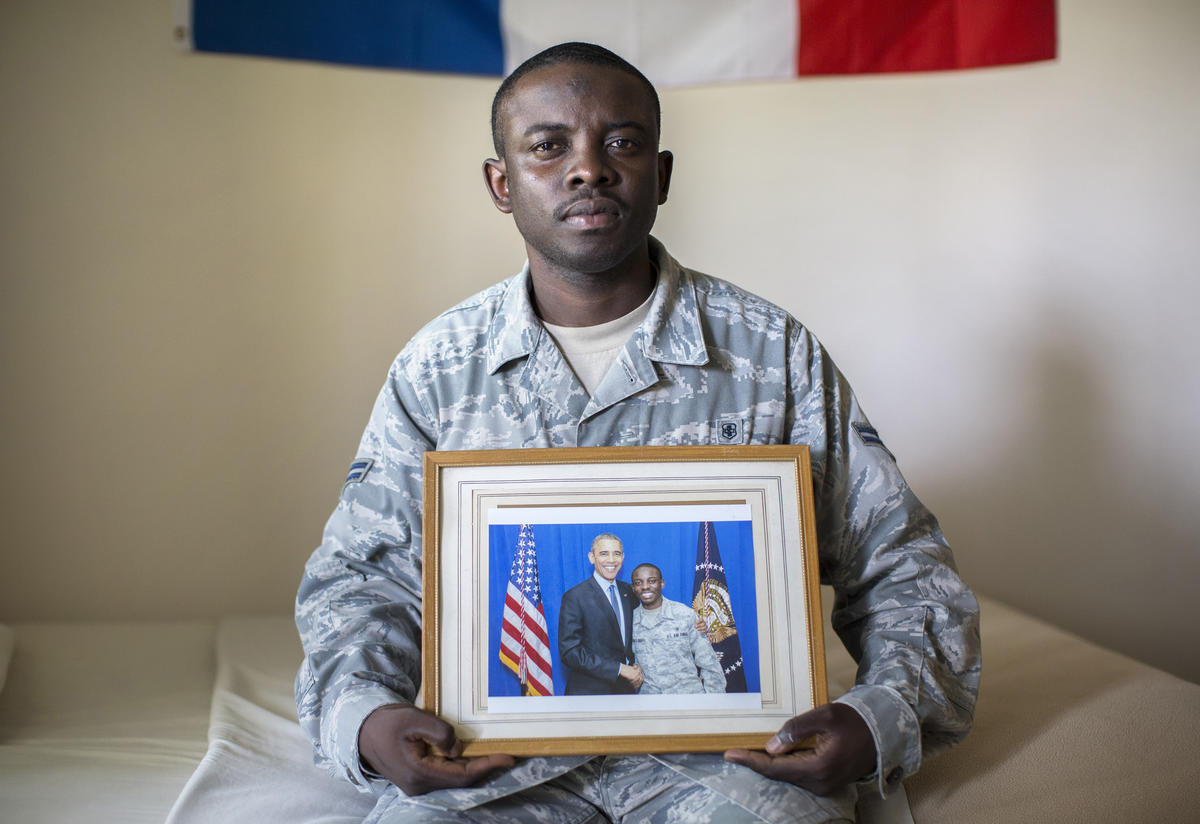 Nelson Rieu holds a photo of himself with Obama