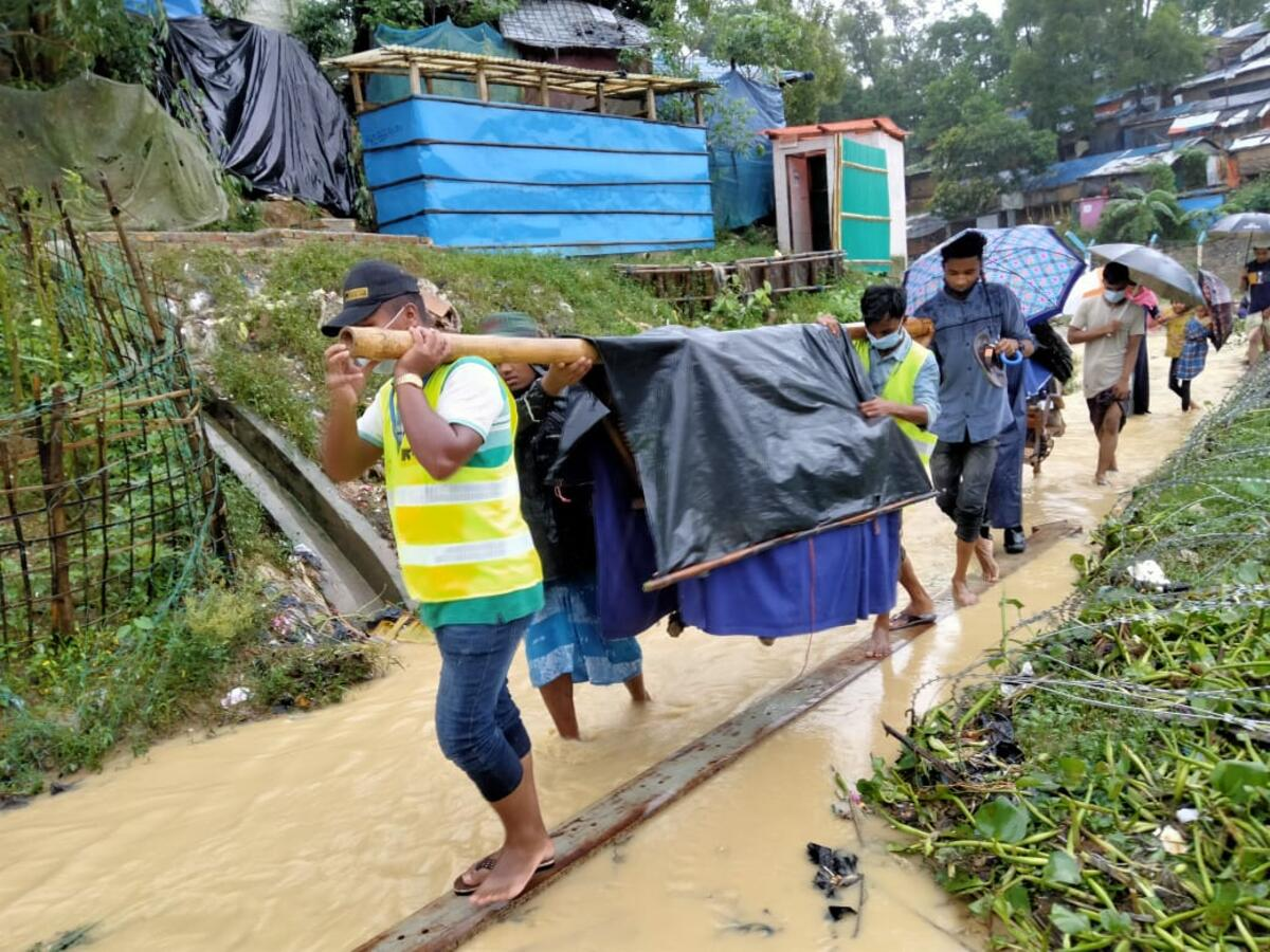 IRC emergency referral unit volunteers carry a patient to a nearby health facility following severe flooding in Cox's Bazar, Bangladesh.