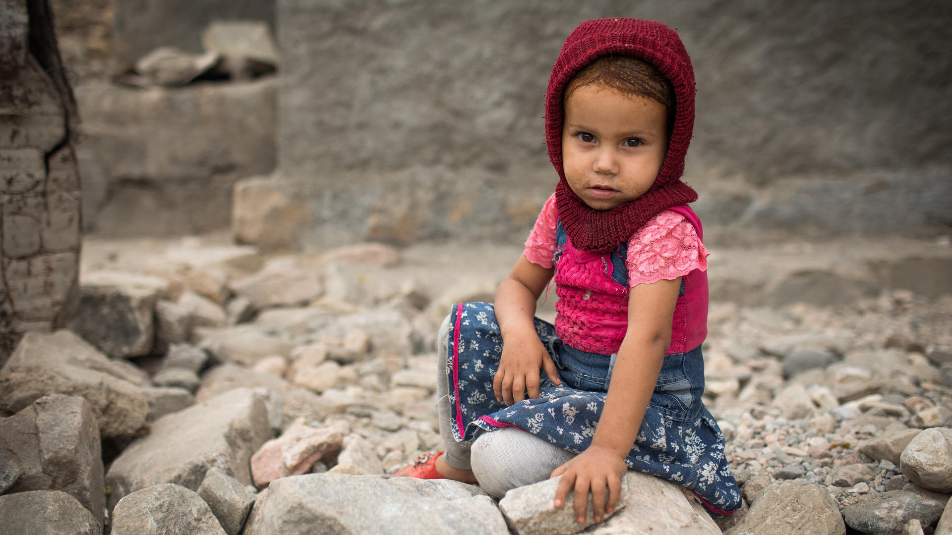 Small girl sits among rubble looking at the camera.