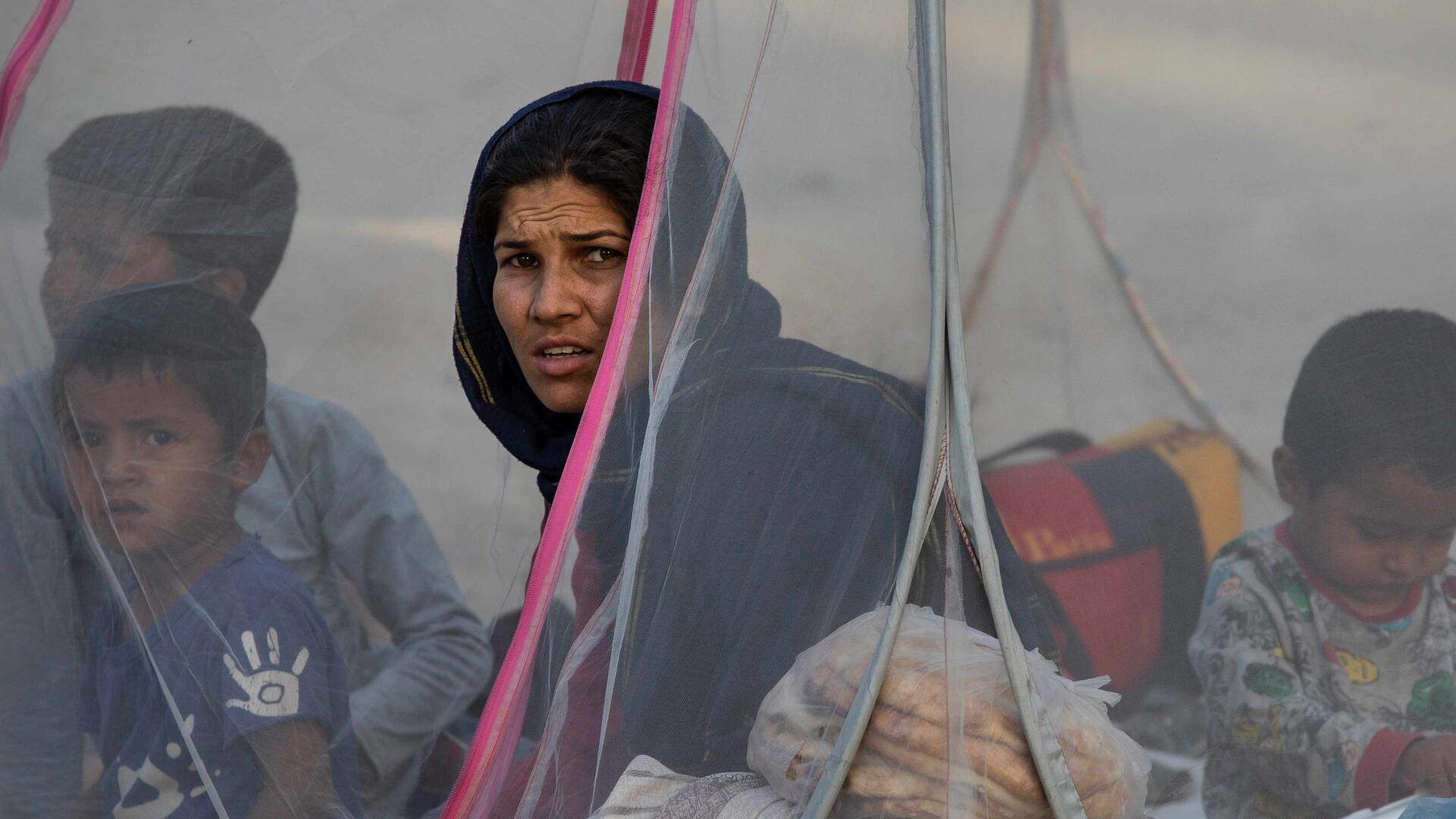 A women sat in a tent with children.