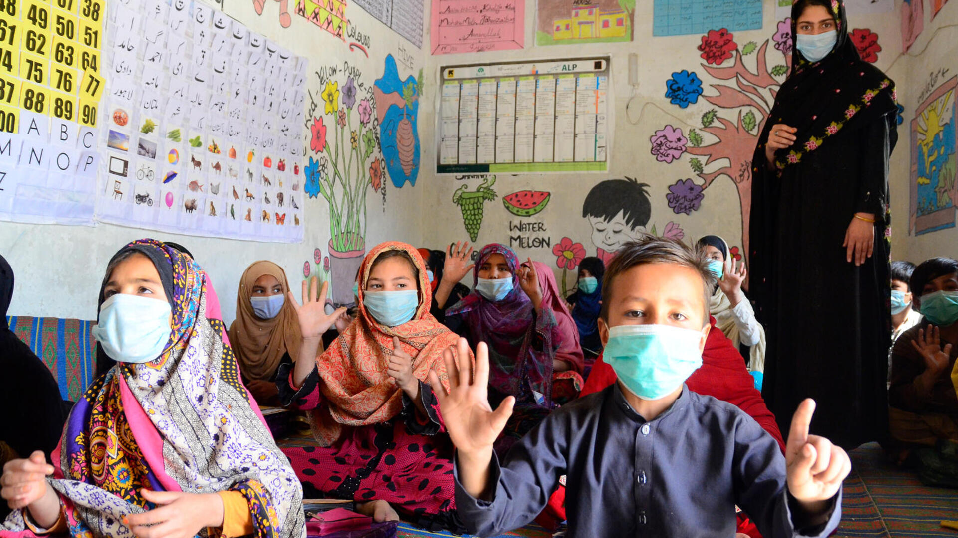 A female teacher in Pakistan with a group of children in a class room all wearing masks
