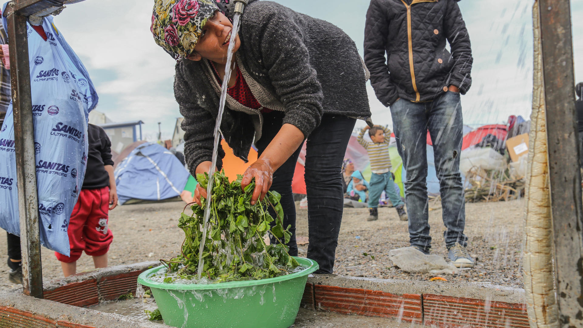 A woman washes vegatables at an IRC-installed water tap in Idomeni, Greece