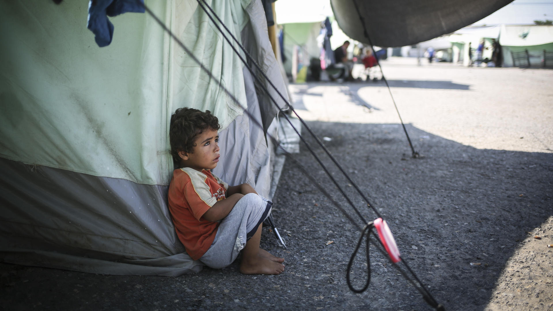 A little boy sits in the shade to escape the mid-day sun at the Alexandria refugee camp in northern Greece