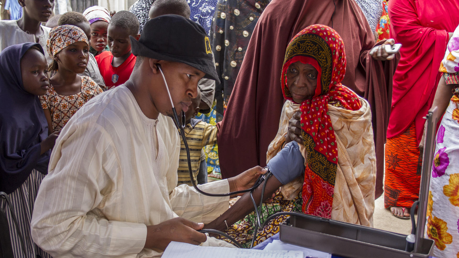 An IRC health worker checks an elderly woman's blood pressure